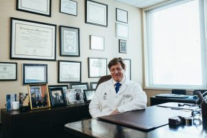 doctor-sitting-in-front-of-his-desk-2182979